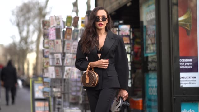 evangelie smyrniotaki wears sunglasses, a black blazer jacket, black pants, white shoes, a vuitton bag, outside elie saab, during paris fashion week... - 3日目点の映像素材/bロール