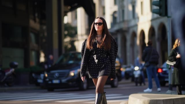 evangelie smyrniotaki wears sunglasses a black dress with printed polka dots black leather boots outside philosophy during milan fashion week... - boot stock videos & royalty-free footage