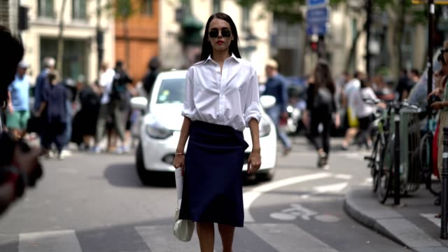 vídeos y material grabado en eventos de stock de evangelie smyrniotaki wears sunglasses, a white shirt, a blue skirt, and pink heels shoes, outside the elie saab show, during paris fashion week -... - camiseta
