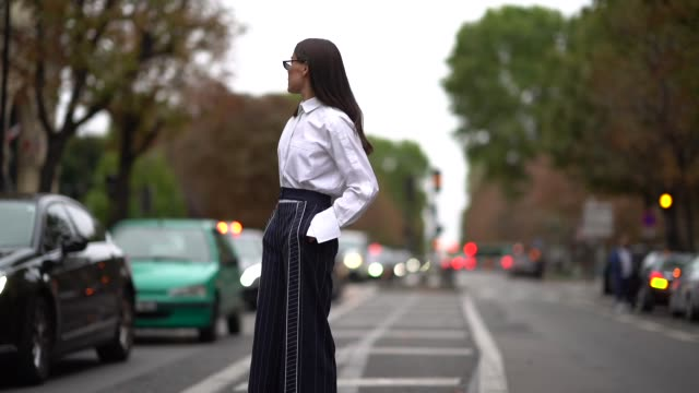 vídeos y material grabado en eventos de stock de evangelie smyrniotaki wears sunglasses, a white shirt, flare striped blue pants, outside valentino, during paris fashion week womenswear... - camiseta