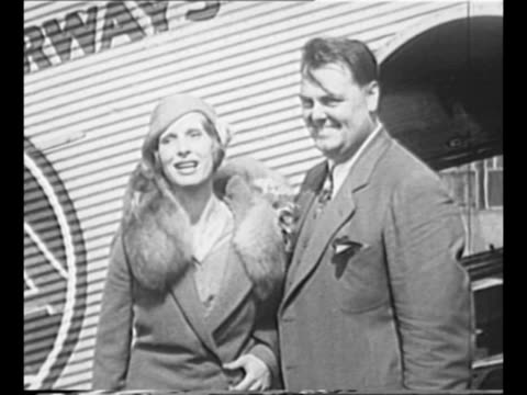 vídeos de stock e filmes b-roll de evangelist aimee semple mcpherson stands at side of airplane with her husband david pharaoh hutton during a stop in newark nj / mcpherson and hutton... - 1931