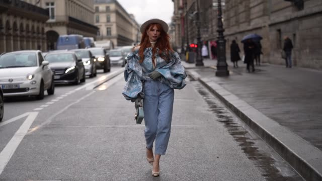 vídeos de stock e filmes b-roll de evelyn kazantzoglou wears a light grey hat, a white turtleneck, a frilly blue jacket with a white lace upper part and ruffled puff sleeves, blue crop... - jaqueta jeans