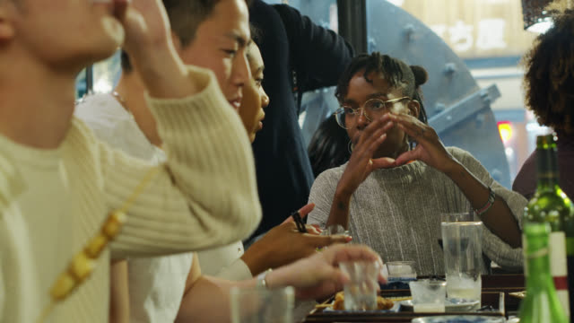 炉端レストランのバーに座っている夜の群衆 - 食事点の映像素材/bロール