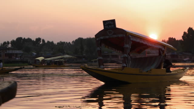 Evening dusk view of a decorated shikara, a type of wooden boat, on Dal Lake of Kashmir