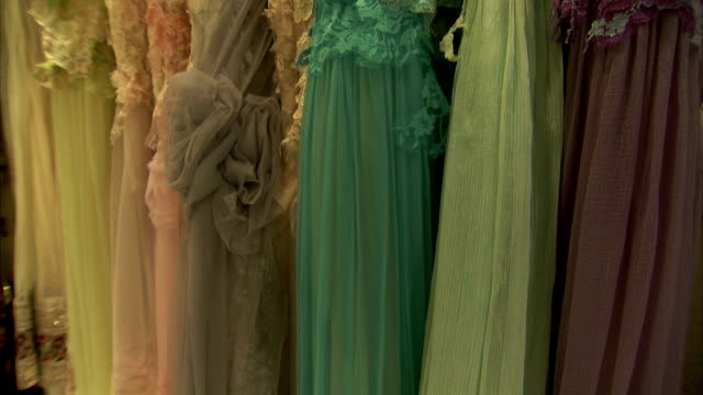 Evening gowns hang in a shop.