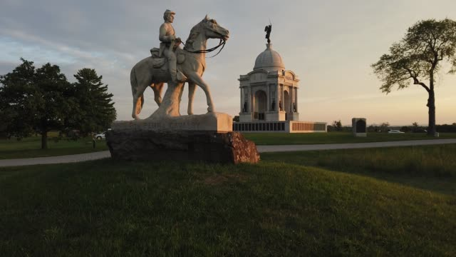 evening light falls on the monument to the 8th pennsylvania cavalry and the state of pennsylvania monument at the gettysburg national military park... - gettysburg stock videos & royalty-free footage