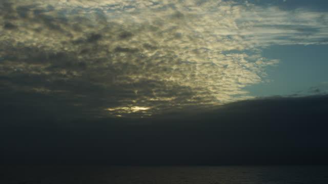 Evening Light Glows Through Altocumulus Clouds Over Ocean