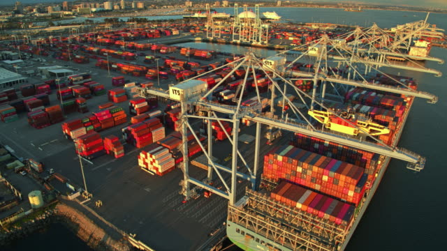 evening light shining on cargo ships and container terminal - aerial - box container stock videos & royalty-free footage