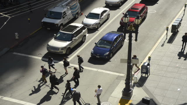 vidéos et rushes de evening rush hour along market street in san francisco, california.  shot from the roof of a building at the corner of market and post streets, commuters and pedestrians compete for space with motor vehicles. - rush hour
