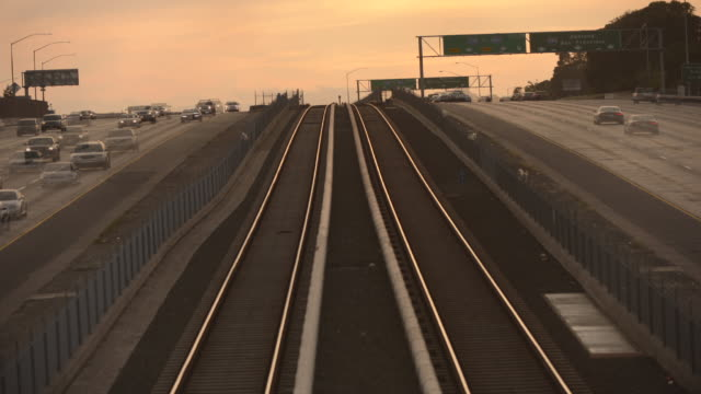 vidéos et rushes de evening rush hour along the bart street line through berkeley, california.  the commuter trains pass one another along the berkeley bart stop. - rush hour
