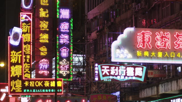 evening street scene in mong kok shopping district - ladenschild stock-videos und b-roll-filmmaterial