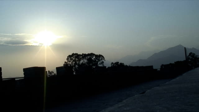 ws evening sun and silhouette of wall, ming tombs, china - ming tombs stock videos and b-roll footage