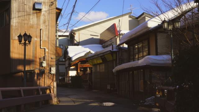 evening sunlight illuminates the japanese style houses and ryokan (traditionaljapaneseinn) stand along the street at shibu onsen (shibu hot spring) yamanouchi-machi, nagano japan on feb. 17 2019. - ryokan stock videos and b-roll footage