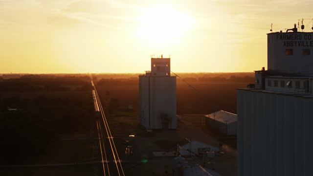 evening sunlight shining on train tracks beside grain elevator - cargo train stock videos & royalty-free footage