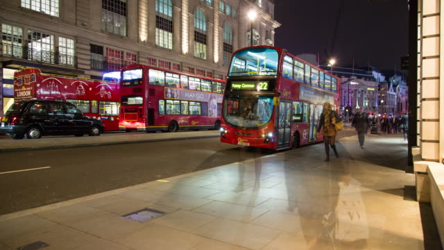 Evening time lapse of heavy pedestrian traffic shopping along Piccadilly, featuring a London bus on the Putney Common (22) route
