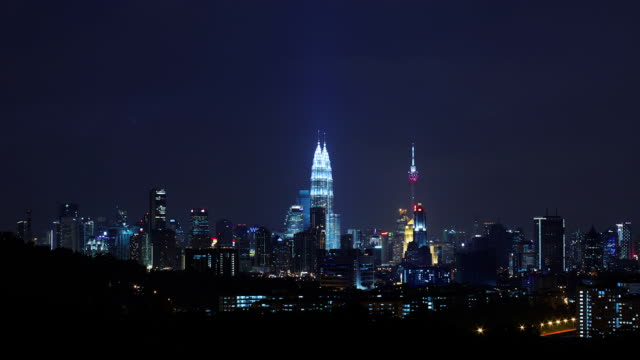 evening timelapse of kuala lumpur skyline, followed by thunderstorm with lightning - petronas twin towers stock-videos und b-roll-filmmaterial