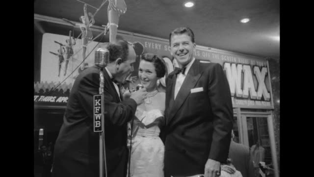 event emcee near microphone labeled kfwb talks to actor ronald reagan and his wife actress nancy davis at the 24hour marathon premiere of 'house of... - 1953 stock videos & royalty-free footage