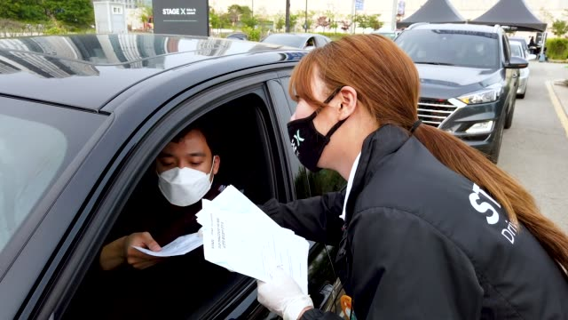 vídeos y material grabado en eventos de stock de event staff checks the temperature of audience while enter at a drive-in musical operation by hyundai motor at stage x drive-in concert as south... - coreano oriental