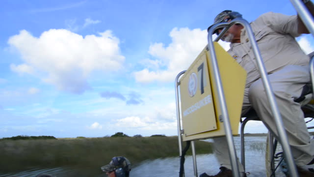 everglades city florida airboat ride fast with tourists riding on water wetlands of everglades at miccosukee indian reserve - everglades national park stock videos & royalty-free footage