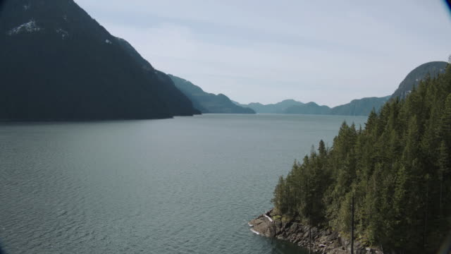vídeos de stock e filmes b-roll de aerial evergreen-covered hillsides and mountains surrounding calm bay waters / vancouver, british columbia, canada - formato letterbox