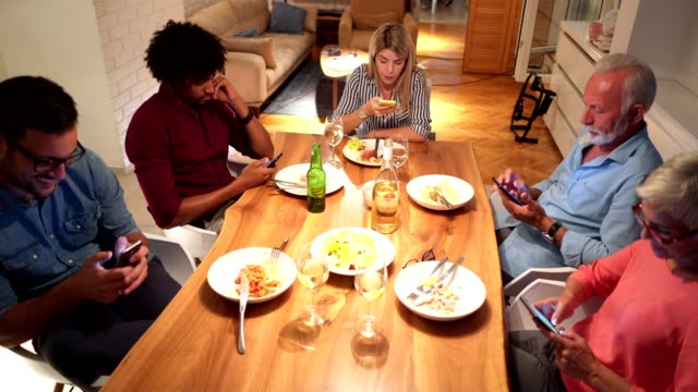 every member of the family holding a mobile phone during a dinner - breakfast table stock videos and b-roll footage