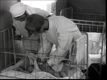 everyday life of workers who build the new factories, pioneers of soviet industrialization . babies dormitory, nurse examine baby, babies having... - 1930 bildbanksvideor och videomaterial från bakom kulisserna