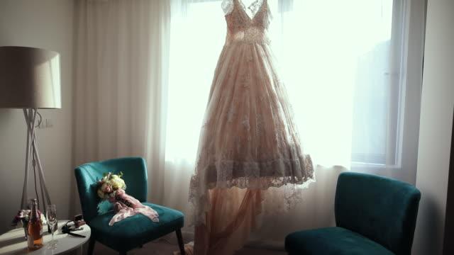 alles ist bereit für die hochzeit. luxus moderne hochzeitskleid hängen am fenster und hochzeit bouquet auf sofa-stuhl - hängen stock-videos und b-roll-filmmaterial