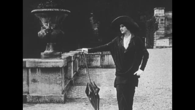 [eve's film review] ms two women in longskirted dresses fashionable in the early 1900s approach walking next to garden pool they toss things into the... - narrow stock videos & royalty-free footage