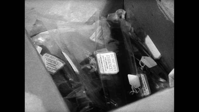 'THE STUART CASE' Evidence in plastic bags being placed in box WS US Department of Justice building Forensic ballistics FBI Technician next to wall...