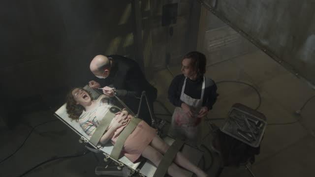 vídeos de stock, filmes e b-roll de evil dentist examining oblivious woman strapped to table / cedar hills, utah, united states - evil