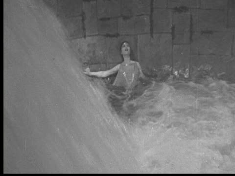 1925 ms cu b/w evil man looking into dungeon through curved lion's eyes, terrified woman waist deep in water screaming - waist deep in water stock videos & royalty-free footage