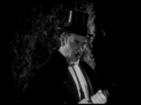 1925 cu b/w evil man wearing cape and top hat in garden at night - schurke stock-videos und b-roll-filmmaterial