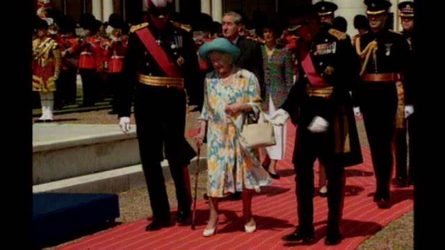Ex royal butler jailed for child abuse Date Unknown EXT Queen Elizabeth the Queen Mother along red carpet flanked by military officers