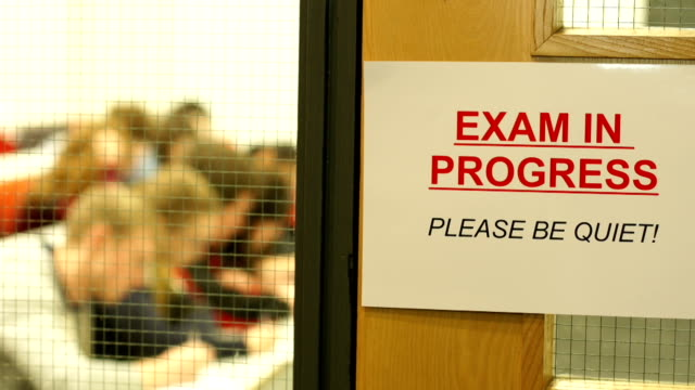 exam in progress sign with students behind - information sign stock videos and b-roll footage