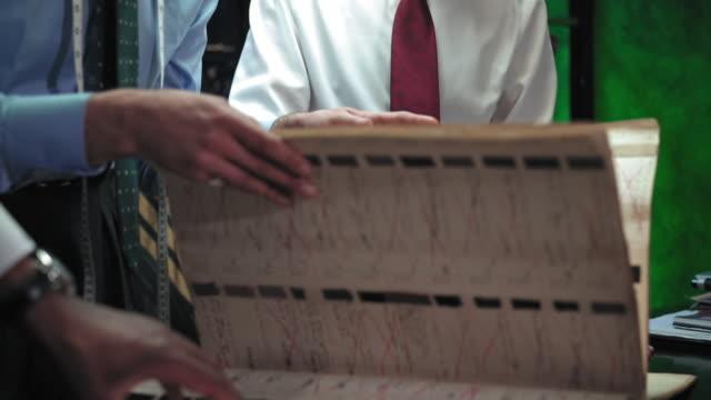 examining fabric swatch book - 生地サンプル点の映像素材/bロール