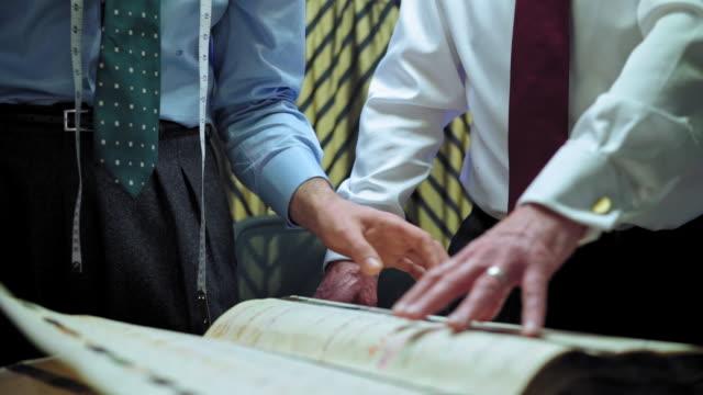 stockvideo's en b-roll-footage met examining fabric swatch book - overhemd en stropdas