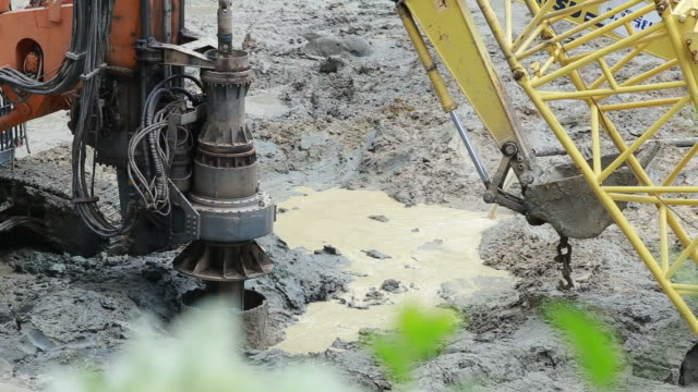 excavator and  pile driver machine drilling rigs for footing building structures - pile driver stock videos and b-roll footage