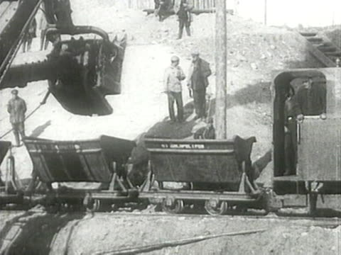 excavator arm loading minecarts at construction site of dnieper hydroelectric station - ex unione sovietica video stock e b–roll