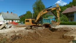 AERIAL Excavator at the building site loading a truck with soil