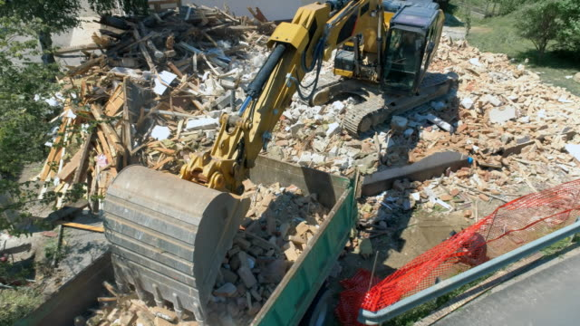 aerial excavator at the demolition site placing debris onto a truck - demolished stock videos & royalty-free footage