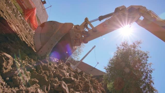 vidéos et rushes de godet d'une excavatrice à creuser dans les débris de construction sous le soleil - pelleteuse