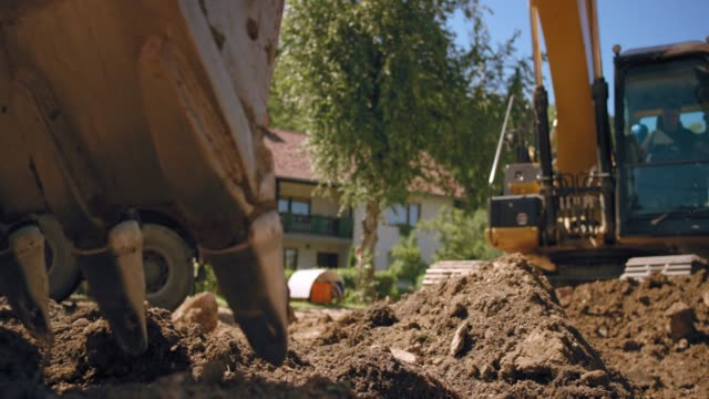 slo mo excavator bucket digging into the soil at the construction site in sunshine - earth mover stock videos & royalty-free footage