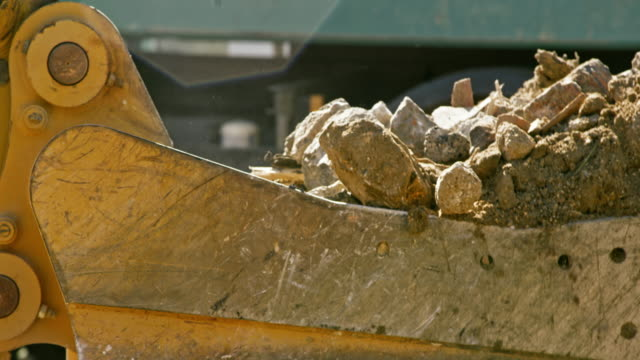 slo mo excavator bucket filling with construction debris in sunshine - construction vehicle stock videos & royalty-free footage