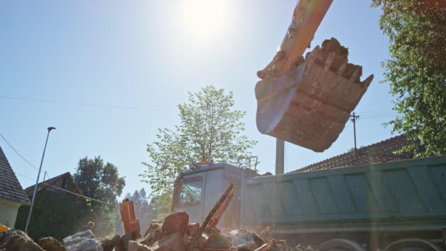 slo mo excavator bucket full of construction debris being loaded onto a truck in sunshine - pietra materiale da costruzione video stock e b–roll