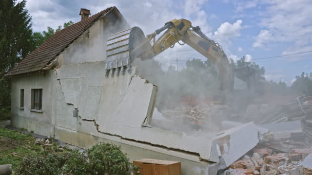 excavator demolishing an old house in the suburbs by pushing its outer walls - demolishing stock videos & royalty-free footage