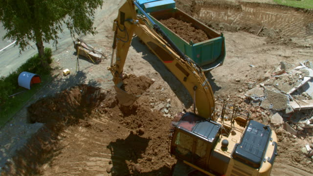 AERIAL Excavator digging into the ground at the construction site and loading the truck with soil