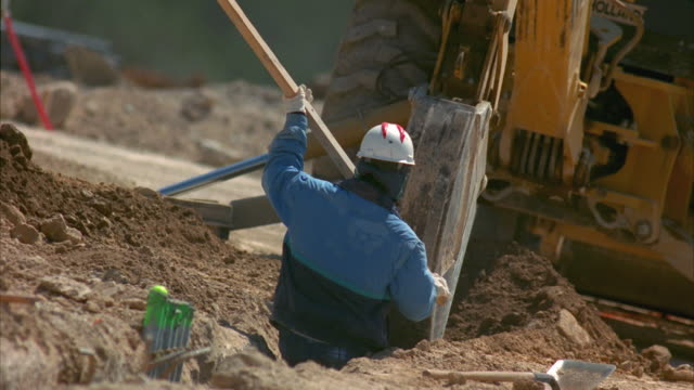 ms pan slo mo excavator digging on construction site, workers working around it / cedar park, texas, usa - 掘る点の映像素材/bロール