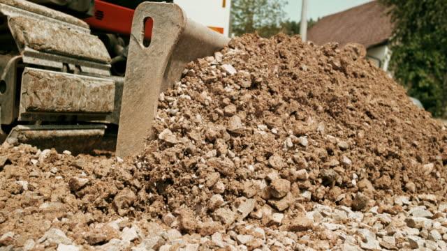 vídeos y material grabado en eventos de stock de slo mo excavadora distribuir piedras machacadas en el sitio de edificio - vehículo comercial terrestre