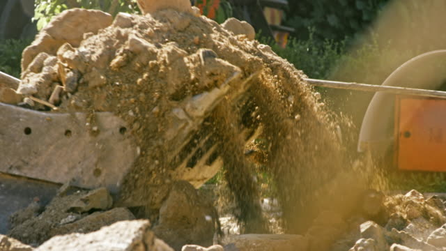 slo mo excavator filling the bucket with demolition debris - earth mover stock videos & royalty-free footage