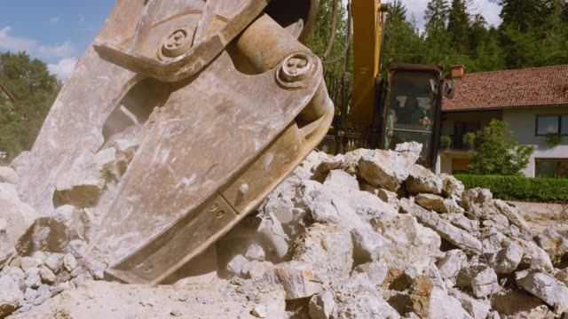 excavator grapple crushing larger pieces of concrete debris in sunshine - bulldozer stock videos and b-roll footage